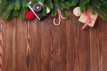 christmas baubles: Christmas tree branch, gift box and camera on wooden table. Top view with copy space