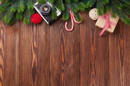 Tak van de kerstboom, cadeau doos en de camera op een houten tafel. Bovenaanzicht met een kopie ruimte