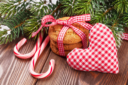 holiday food: Christmas gingerbread cookies, candy cane and toy heart on wooden table