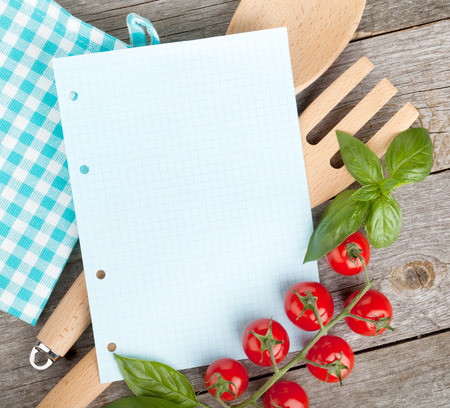 italian cuisine: Blank notepad paper for your recipes with tomatoes and basil on wooden table Stock Photo