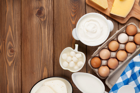 cream cheese: Dairy products on wooden table. Sour cream, milk, cheese, egg, yogurt and butter. Top view with copy space