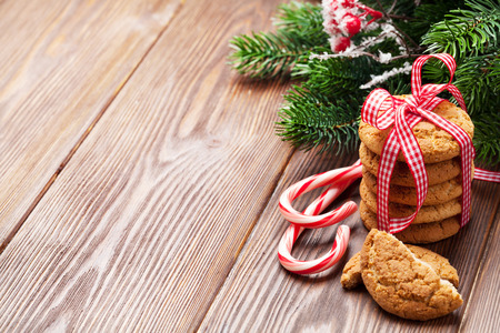 candy cane: Christmas gingerbread cookies, candy cane and tree branch on wooden table. Top view with copy space Stock Photo
