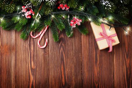 Dennenboom tak met kerstverlichting, geschenkverpakking en snoep stokken op houten achtergrond met kopie ruimte