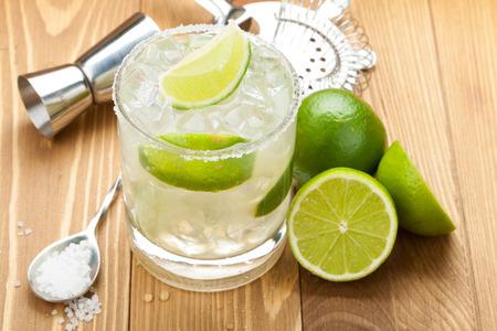 margarita cocktail: Cóctel clásico margarita con borde salado en mesa de madera con limas y utensilios de bebidas
