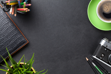 green and black: Office leather desk table with camera, supplies, coffee cup and flower. Top view with copy space