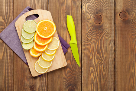 space wood: Sliced citruses on cutting board. Top view over wood table background with copy space