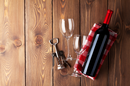 Red wine bottle, glasses and corkscrew on wooden table background. Top view with copy space