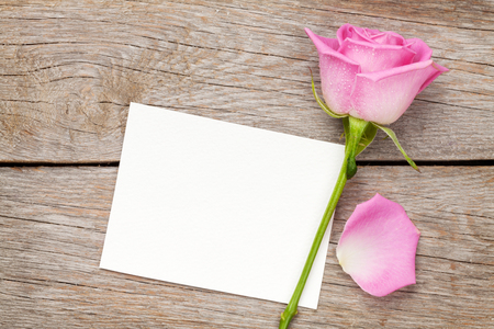 romantic picture: Valentines day greeting card or photo frame and pink rose over wooden table. Top view with copy space