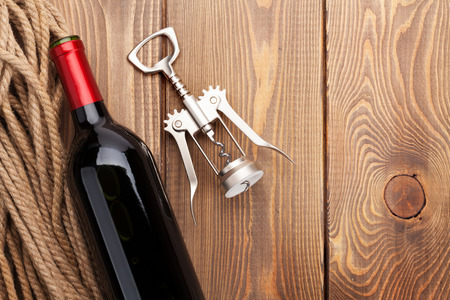 wine glasses: Red wine bottle and corkscrew on wooden table background. Top view with copy space Stock Photo