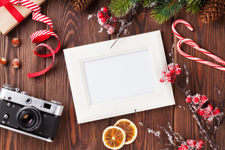 camera: Blank photo frame with christmas gift box, pine tree and camera on wooden table. Top view Stock Photo