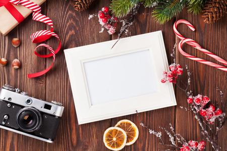 cajas navideñas: Marco de fotos en blanco con caja de regalo de la Navidad, árbol de pino y la cámara en la mesa de madera. Vista superior