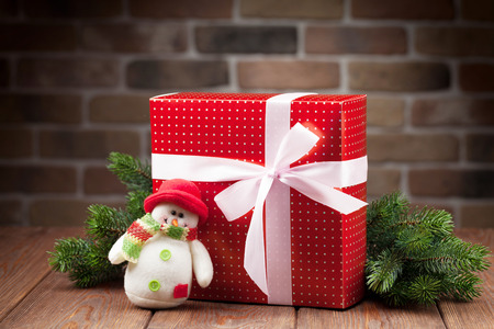 christmas toy: Christmas gift box, snowman toy and fir tree branch on wooden table