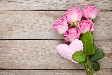 Pink roses bouquet and handmaded heart toy over wooden table. Top view with copy space Foto de archivo