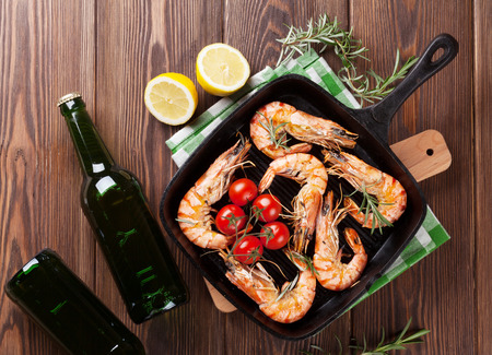 tiger shrimp: Grilled shrimps on frying pan and beer. Top view