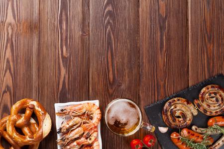 camaron: Taza de cerveza, camarones a la parrilla, salchichas y pretzel en mesa de madera. Vista superior con espacio de copia Foto de archivo
