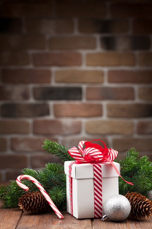 cane: Christmas gift box and fir tree branch on wooden table. View with copy space