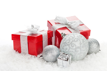 Christmas baubles and red gift boxes over snow with copy space