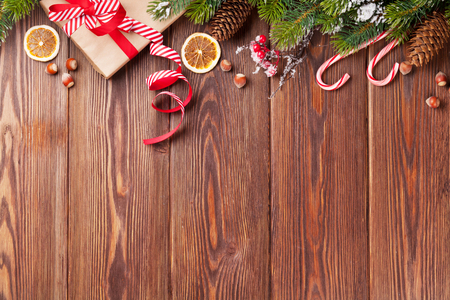 top of the year: Christmas gift box, food decor and fir tree branch on wooden table. Top view with copy space