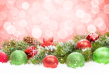 pink decorations: Christmas tree and bauble decor on snow with bokeh background for copy space