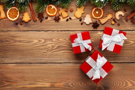 naranja arbol: Cajas de regalo sobre fondo de madera de la Navidad con el �rbol de abeto de la nieve, especias y galletas de jengibre