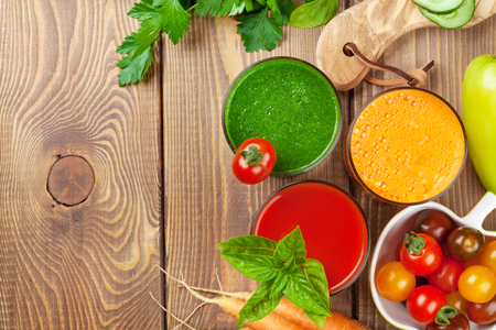 nature green: Fresh vegetable smoothie on wooden table. Tomato, cucumber, carrot. Top view with copy space