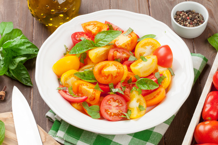 cocina saludable: Fresh colorful tomatoes and basil salad on wooden table