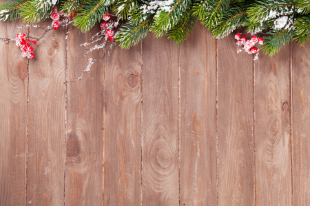 Christmas wooden background with snow fir tree. View with copy space