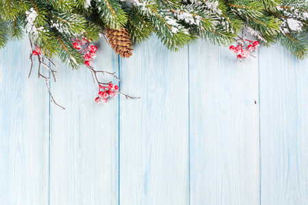 Kerstmis houten achtergrond met sneeuwspar en hulstbes Stockfoto