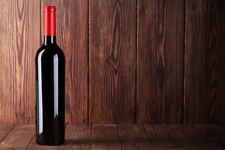 wine glasses: Red wine bottle on wooden table. View with copy space