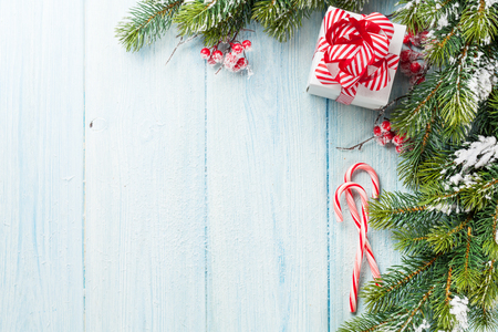 background box: Christmas gift box, candy cane and fir tree branch on wooden table. Top view with copy space Stock Photo