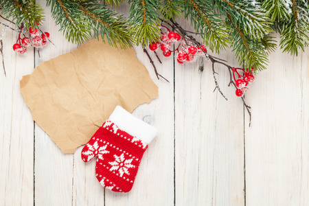 fir tree: Christmas wooden background with fir tree and mitten decor. View from above with paper for copy space Stock Photo