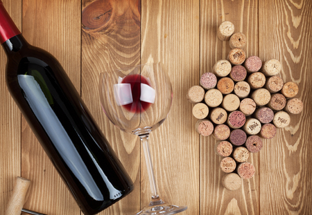 closed corks: Red wine bottle, glass and grape shaped corks on wooden table background Stock Photo