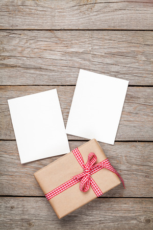 frame  box: Photo frame cards and gift box with ribbon over wooden table background