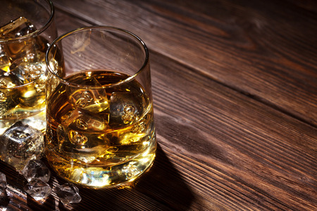 whiskey glass: Glasses of whiskey with ice on wooden table with copy space