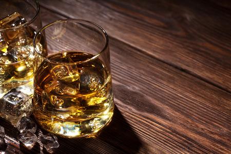 whisky: Verres de whisky avec de la glace sur la table en bois avec copie espace