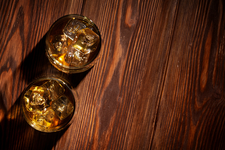 copy: Glasses of whiskey with ice on wooden table. Top view with copy space