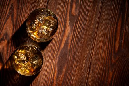 kopie: Sklenice whisky s ledem na dřevěném stole. Pohled shora s kopií vesmíru