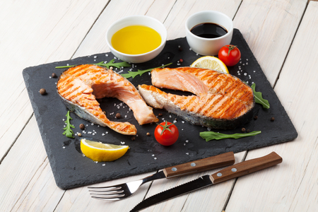 condiments: Grilled salmon, salad and condiments on wooden table