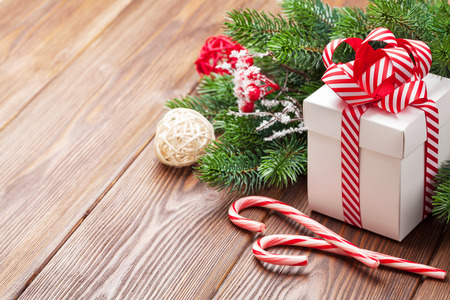 christmas gift box: Christmas gift box, candy cane and fir tree branch on wooden table. View with copy space