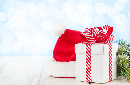 christmas gift box: Christmas gift box, santa hat and fir tree branch on wooden table with bokeh background for copy space