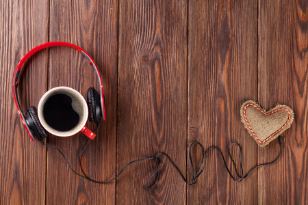 Radio: Heart toy with headphones and coffee cup on wooden table with copy space. Valentines day concept.