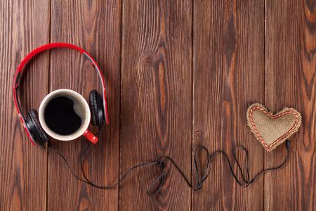 Herz-Spielzeug mit Kopfhörer und Kaffeetasse auf Holztisch mit Kopie Raum. Valentinstag-Konzept. Standard-Bild - 47226938