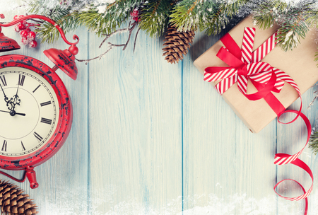 fir tree: Christmas wooden background with snow fir tree, alarm clock and gift box. Vintage toned Stock Photo