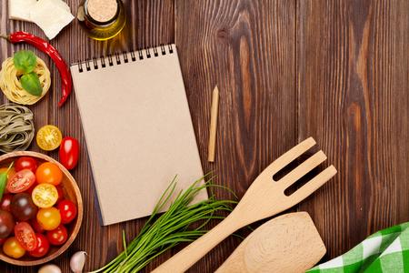 Italiaans eten koken ingrediënten. Pasta, groenten, kruiden. Bovenaanzicht met kladblok voor kopie ruimte
