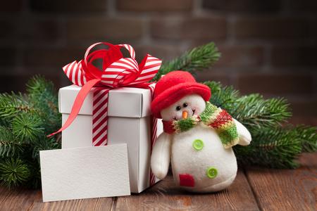cajas navide�as: caja de regalo de la Navidad, juguete mu�eco de nieve, tarjeta de felicitaci�n y la rama de abeto en mesa de madera