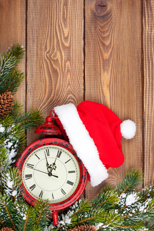 twelve month old: Christmas wooden background with clock, snow fir tree and santa hat