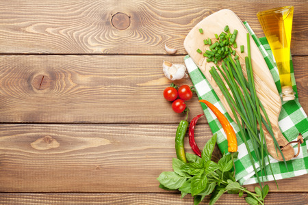italian cuisine: Cooking ingredients on wooden table. Spring onion, basil, chili, olive oil. Stock Photo