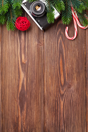 camera: Christmas tree branch, camera and candy cane on wooden table. Top view with copy space Stock Photo