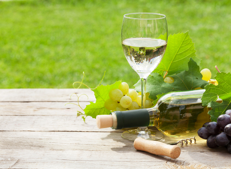 White wine, wine bottle and grape on wooden table with copy space