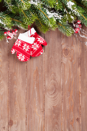 background wood: Christmas wooden background with snow fir tree and mittens decor. View with copy space